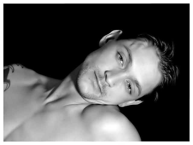 portrét muže nahýbajícího se před kamerou